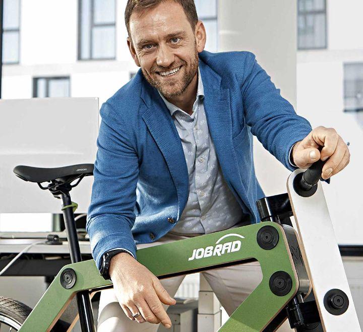 Ulrich Prediger lehnt sich über ein grünes Holzbike