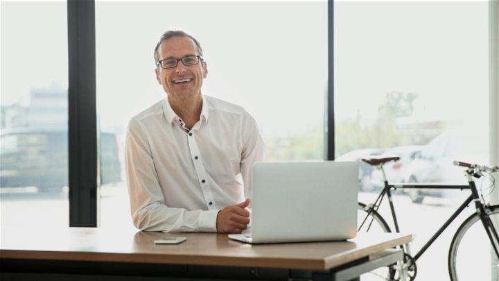 Arbeitgeber am Schreibtisch, lächelnd mit Fahrrad im Hintergrund