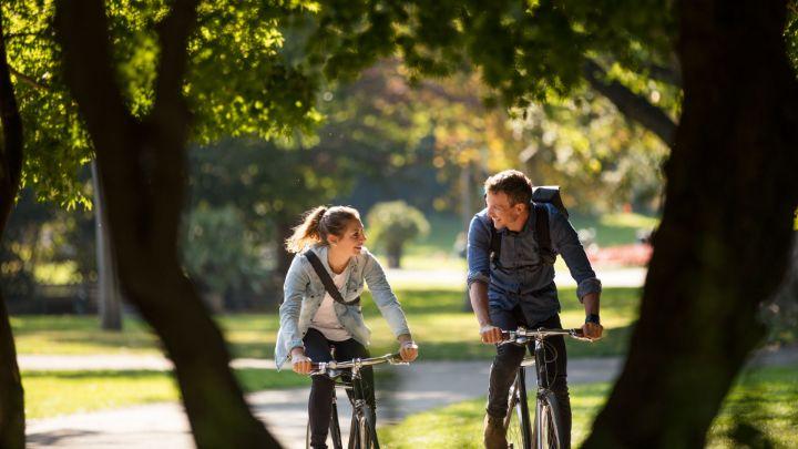 Zwei Radler fahren gemütlich durch den Park und unterhalten sich