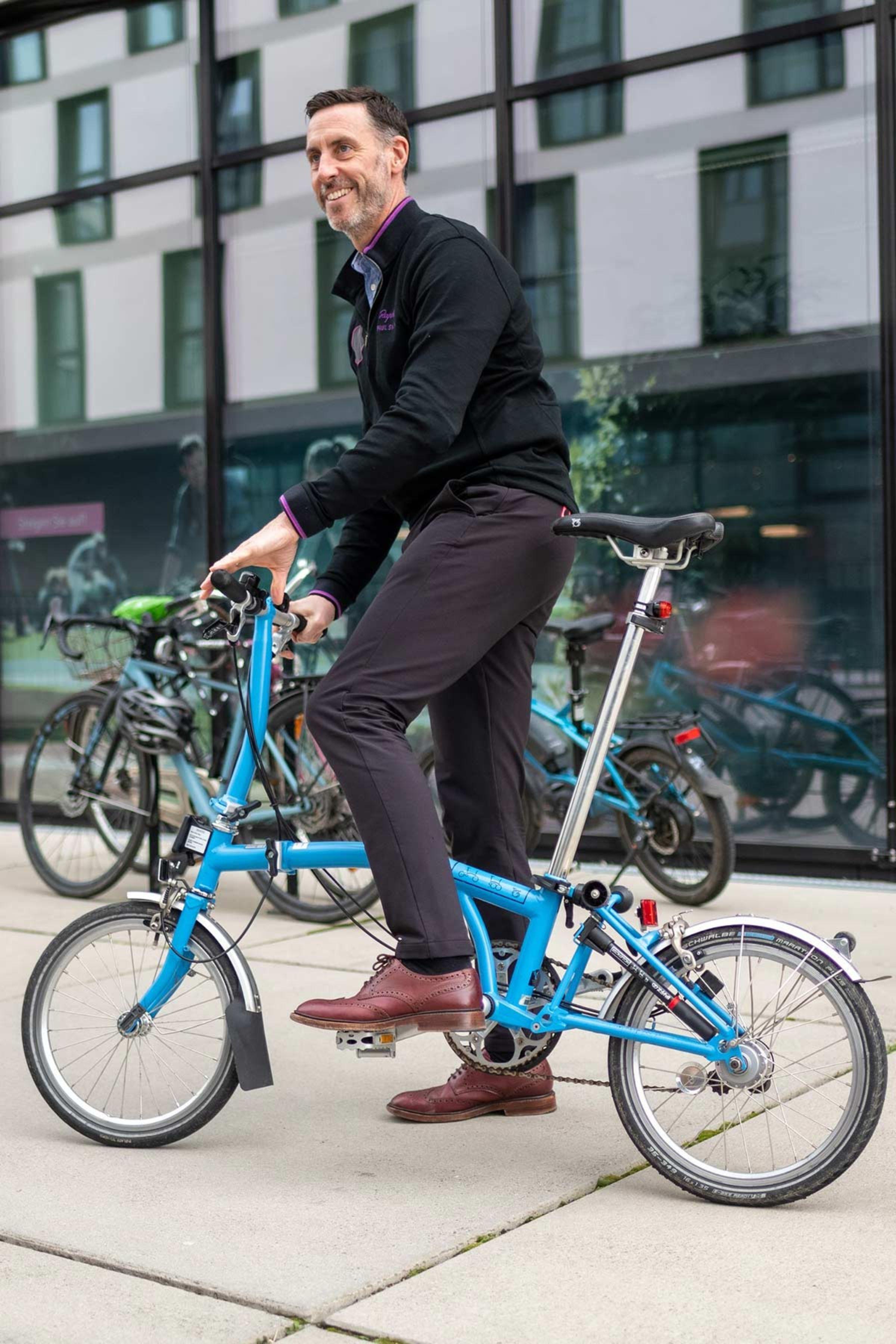 Daniel Gillborn mit blauem Faltrad