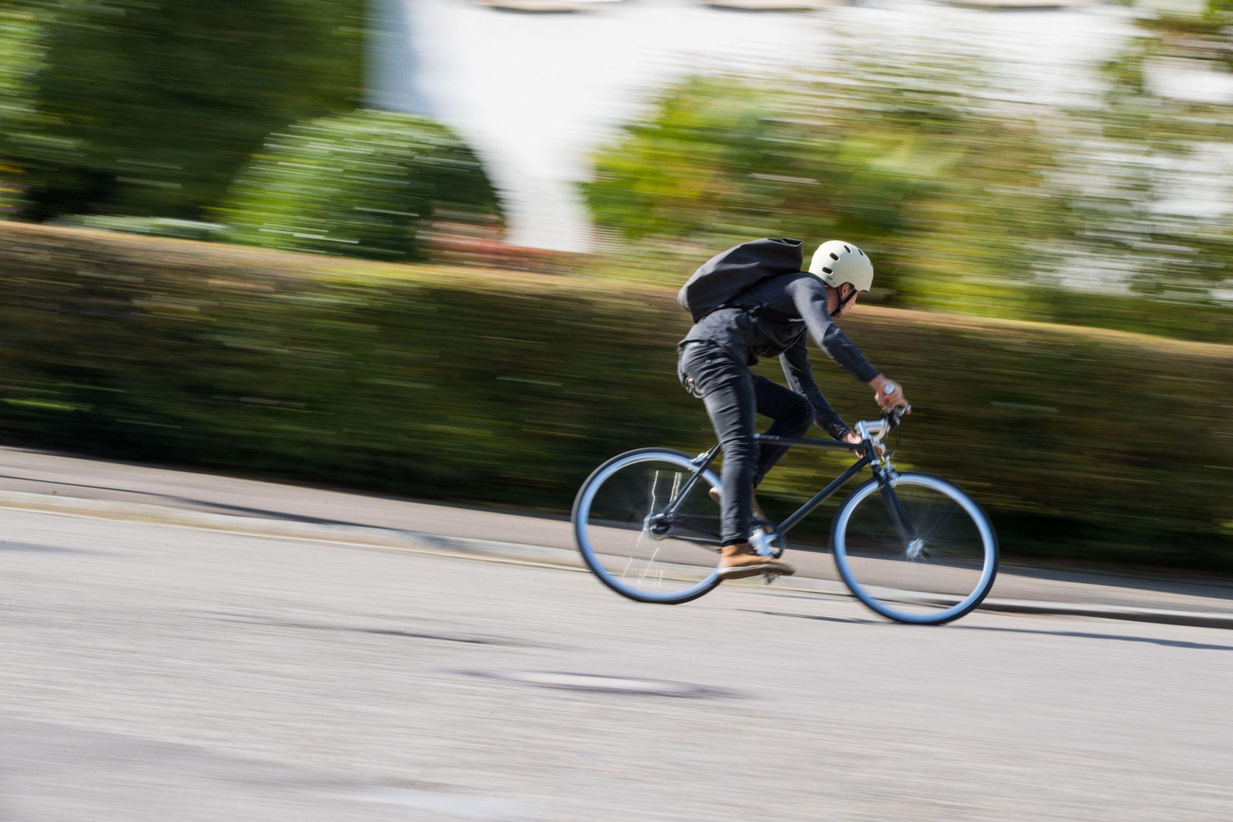 JobRadler mit Helm fährt schnell